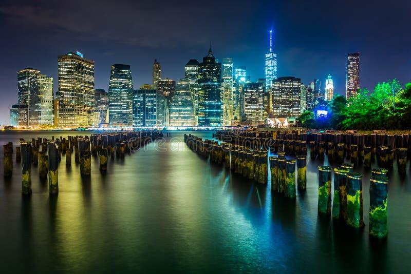 Pilhas do cais e a skyline de Manhattan na noite, vista do ribeiro foto de stock