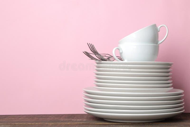 Pilhas dos utensílios de mesa cerâmicos brancos, placas, pires, copos em um fundo cor-de-rosa kitchenware imagens de stock