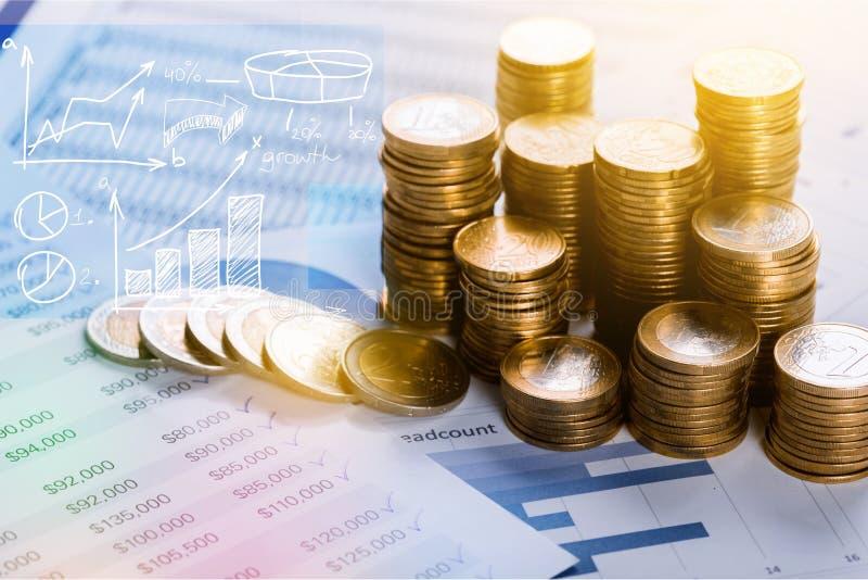 Pilhas douradas das moedas no fundo azul fotografia de stock