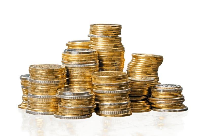 Pilhas douradas das moedas no fundo branco foto de stock