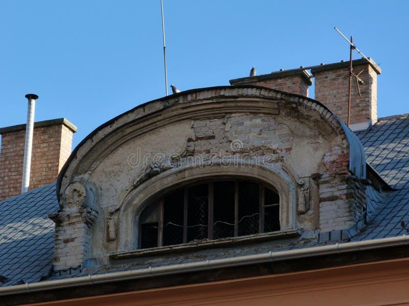 Pilhas e chaminés do tijolo e trapeira velho arqueado no telhado inclinado do metal foto de stock royalty free