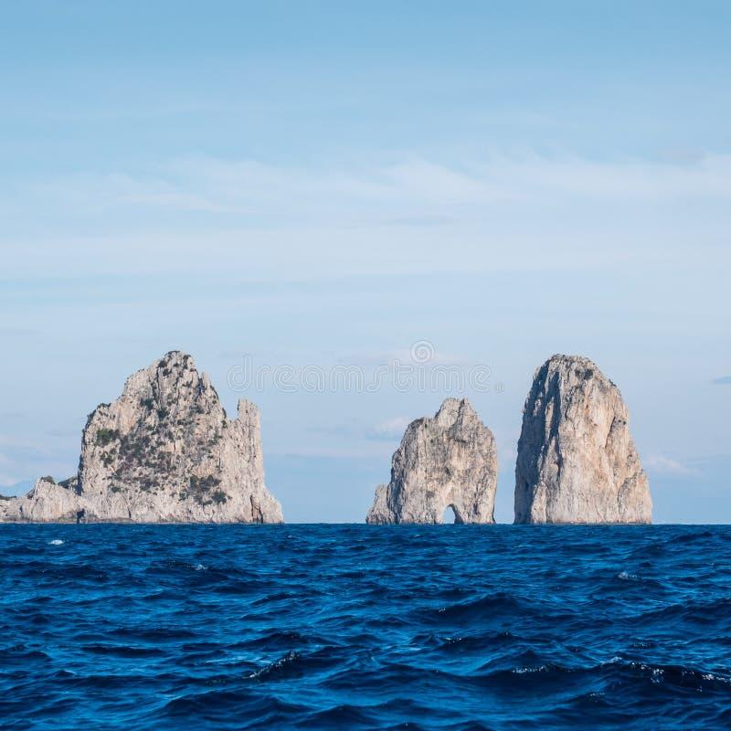 Pilhas famosas do mar com arco, faraglioni, fora da costa de Capri na baía de Nápoles no mar Mediterrâneo, Itália foto de stock