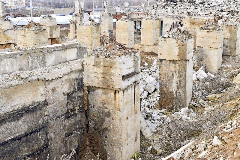 Pilhas poderosas de uma fundação com o rebar de projeção no fundo de uma construção industrial arruinada fotos de stock royalty free