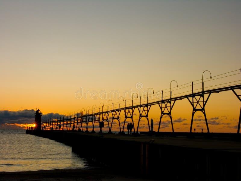 Pilier avec la passerelle et phare au coucher du soleil photographie stock