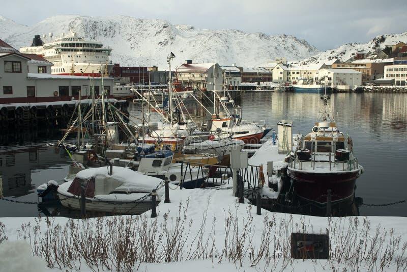 Pilier avec les bateaux amarrés couverts dans la neige, de docks commerciaux à l'arrière-plan photo stock