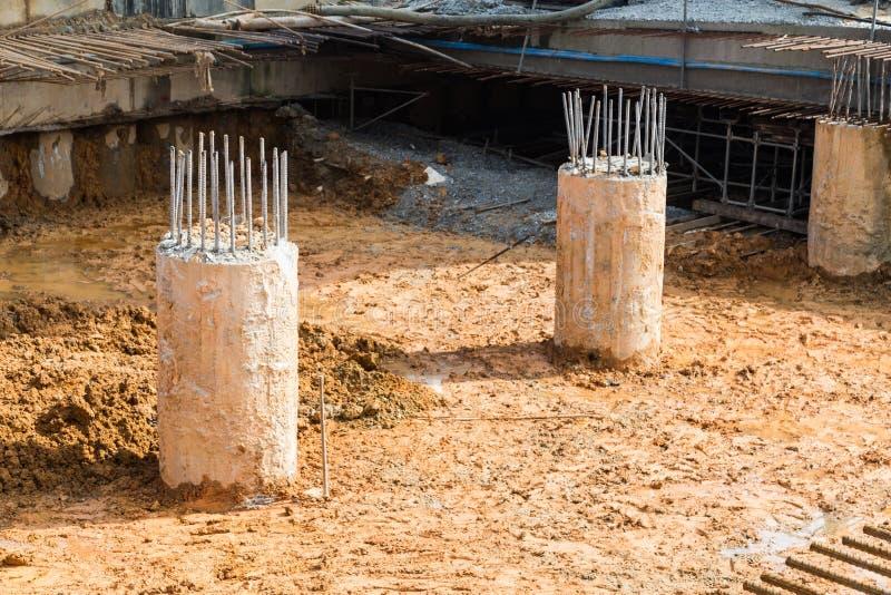 Pilier concret avec les tiges en acier sur le chantier de construction moulu de saleté photos stock
