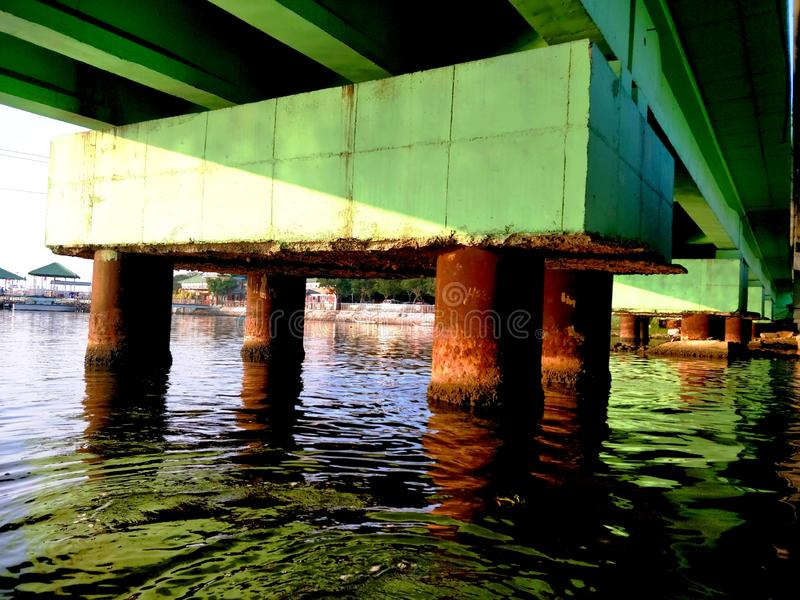 Pilier d'un pont fini d'angle faible avec la réflexion de l'eau courante images stock