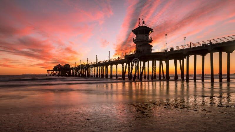 Pilier de Huntington Beach pendant un coucher du soleil rouge et orange image stock