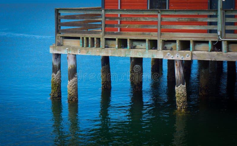 Pilier de pêche avec le bâtiment rouge photographie stock libre de droits