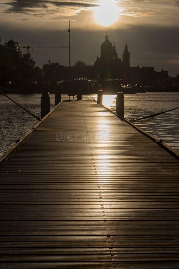 Pilier en bois avec des bateaux au coucher du soleil dans le dock d'Amsterdam Silhouettes de ville d'Amsterdam en égalisant la lu images libres de droits