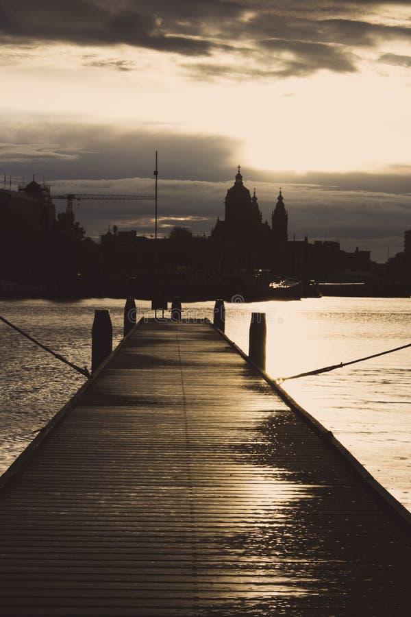 Pilier en bois avec des bateaux au coucher du soleil dans le dock d'Amsterdam Silhouettes de ville d'Amsterdam en égalisant la lu image libre de droits