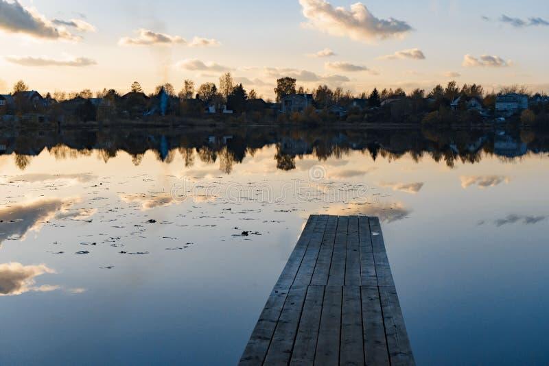 Pilier en bois avec des feuilles sur le lac tranquille en automne photographie stock libre de droits