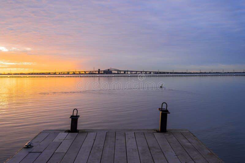 Pilier en bois de bateau menant au lever de soleil coloré vibrant au-dessus du TR photos stock