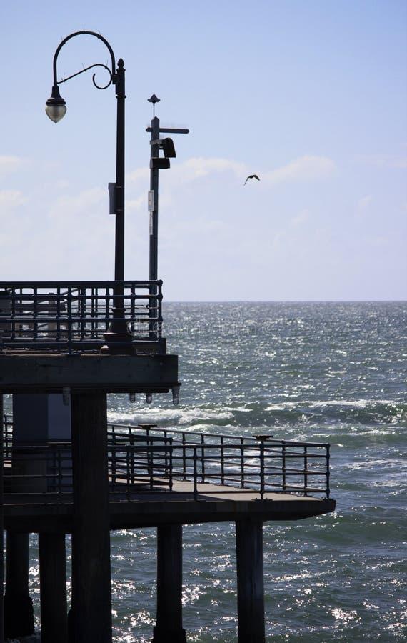 Pilier et lampadaire donnant sur l'océan photo stock