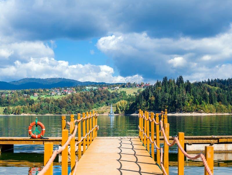 Pilier vers le lac avec la bouée de sauvetage, les montagnes et le ciel nuageux, la vue du voilier et le village photo libre de droits