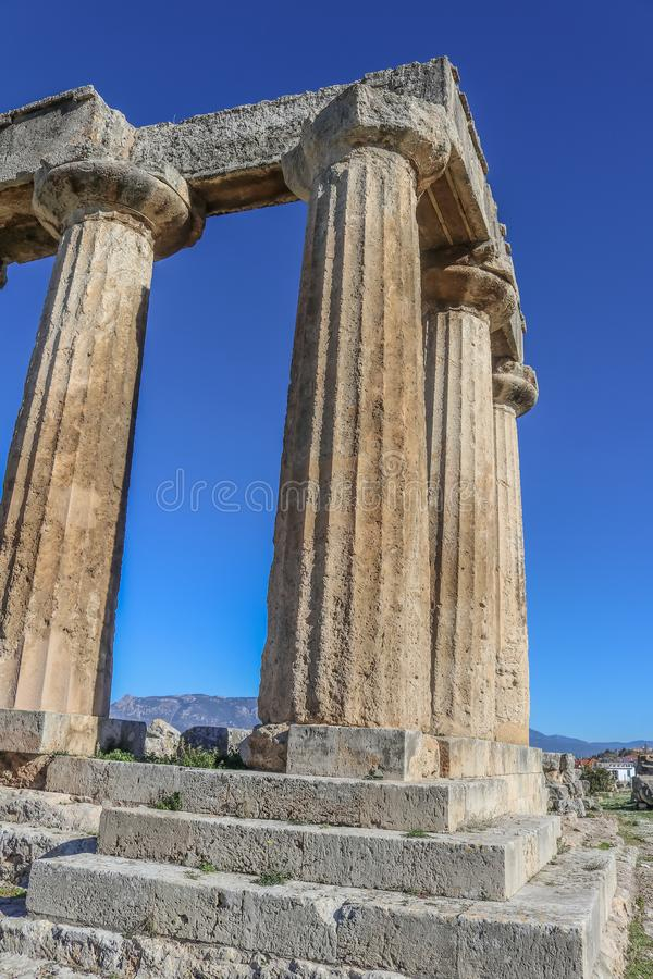 Piliers de temple d'Apollo à Corinthe antique sur la péninsule Grèce de Péloponnèse - regardant la perspective de diminution et photos stock