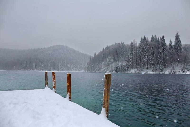 Piliers en bois gardant le lac d'hiver photographie stock libre de droits