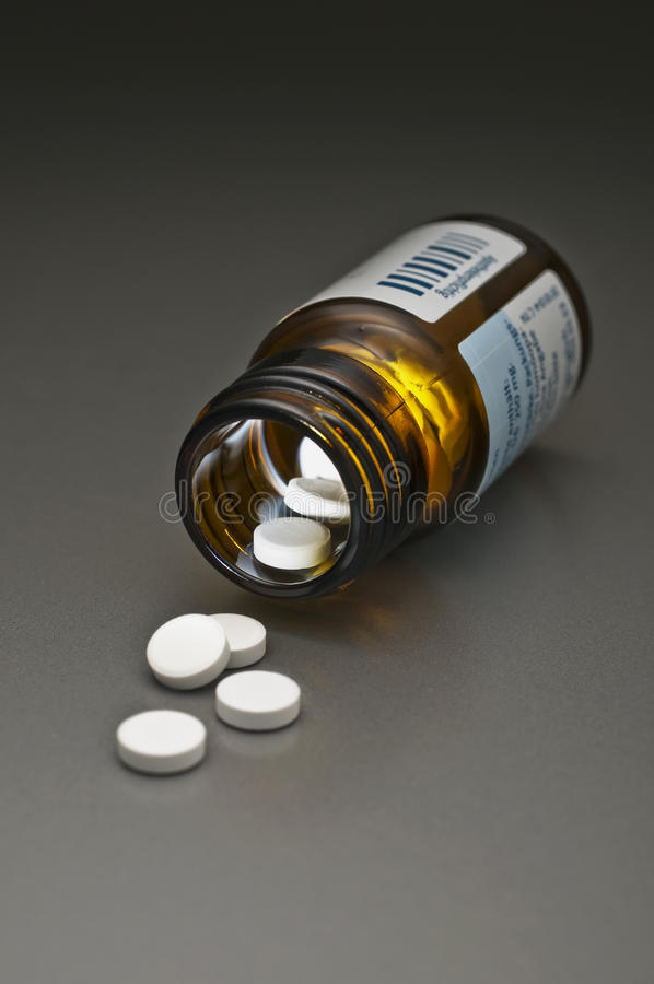Pill bottle. Tablets with open pill bottle on grey background stock photos