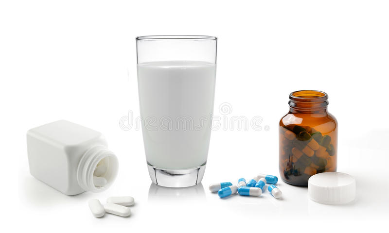 Pill bottle and glass of milk on white background royalty free stock photography