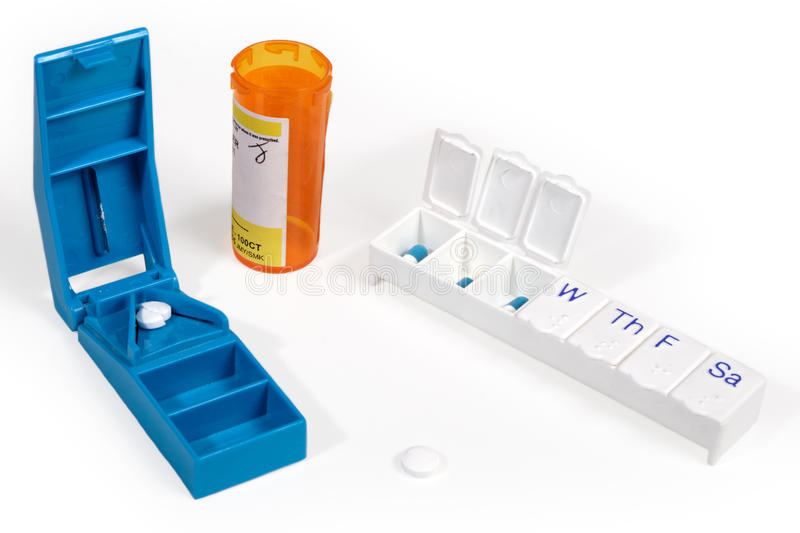 Pill cutter and storage. Pill cutter and weekly storage box with medicine bottle and pills stock images