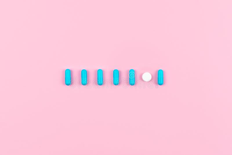 Bright blue pills in line, row on pink background. Medicines, drugs, pharmacy concept. Flat lay, top view, minimal style stock photos