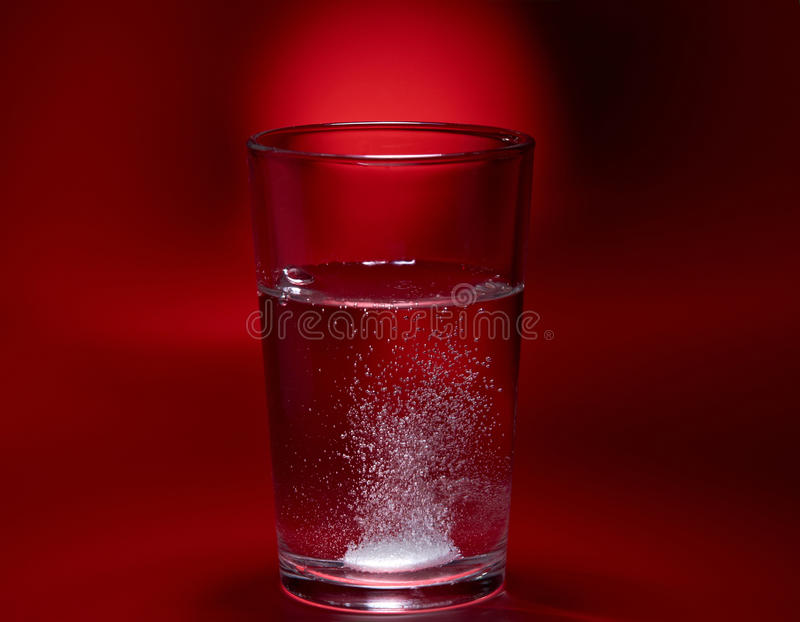 Pill in a glass royalty free stock images