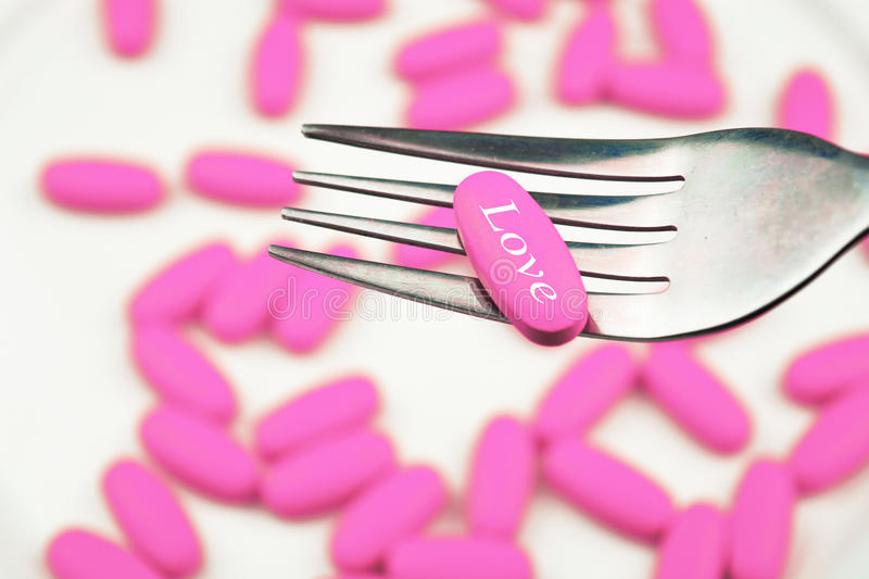 Pill of love on a fork. Pink pill stock photos