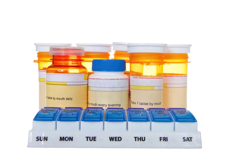 Pill organizer with med bottles lined up behind stock photography