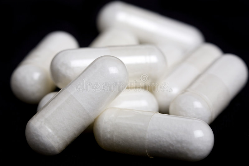 Pill Pile. A pile of white capsule pills stock image