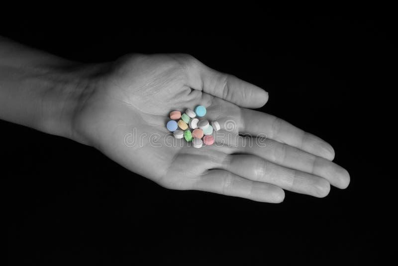 Daily Pill Regimen - Pills in Female Hand. Female hand holding an assortment of generic pills stock photo