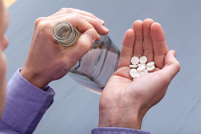 Pill-taker with handful. A pill-taker with a handful of tablets and vodka stock photos