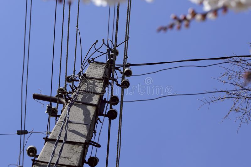 A pillar with electrical wires against a blue sky. stock photos