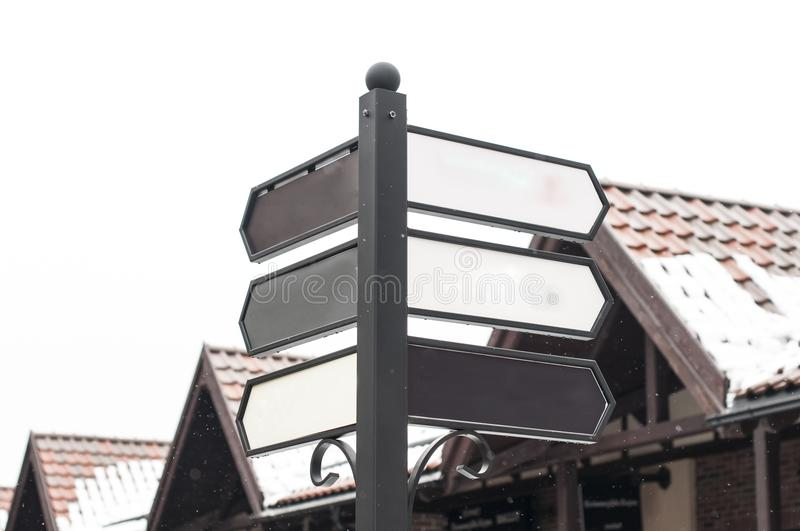 Pillar with empty street signs. Against the background of the roofs of houses royalty free stock photo
