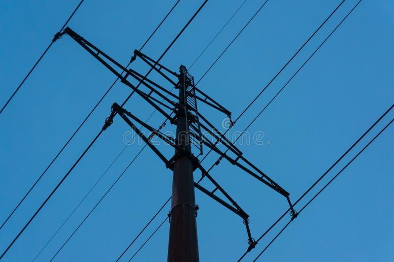 Pillar high-voltage power lines against the evening blue sky stock photos
