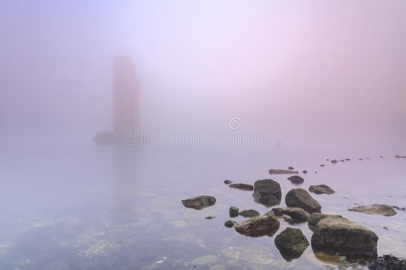 Pillar of a storm surge barrier in fog during sunset. One of the remaining pillars of the storm surge barrier standing in water during a heavy dense foggy winter royalty free stock photo