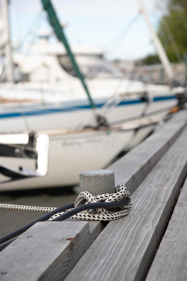 Pillar for tying boats on a wooden pier. Bollard with two ropes on the pier fishing boats. in the background blurred boats and stock photo