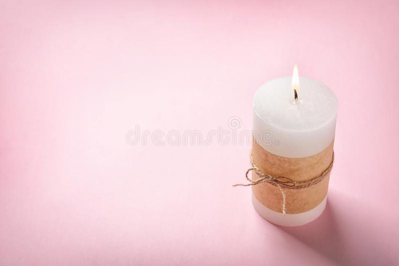 Pillar wax candle burning. On color background stock photography