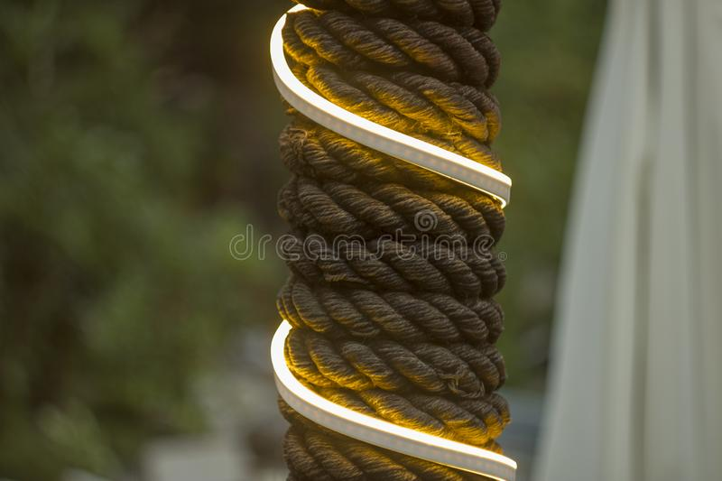 A pillar wrapped with thick rope. yellow white glowing garland with a rope against a background of blurred green wood and curtains stock image