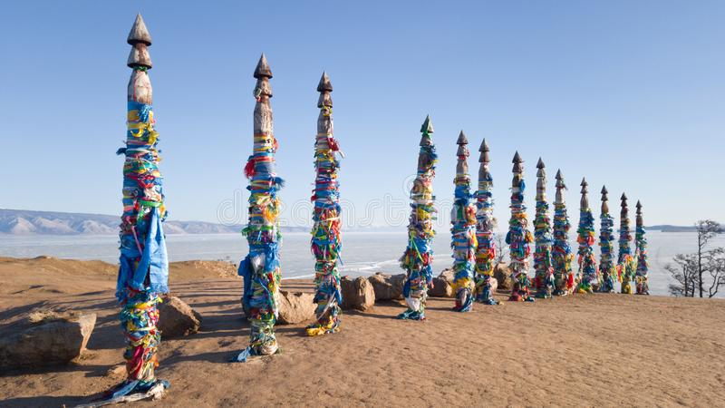 Pillars with colored ribbons on them in the place of power on lake Baikal - Cape Burhan near the village of Khuzhir. Lake Baikal stock image