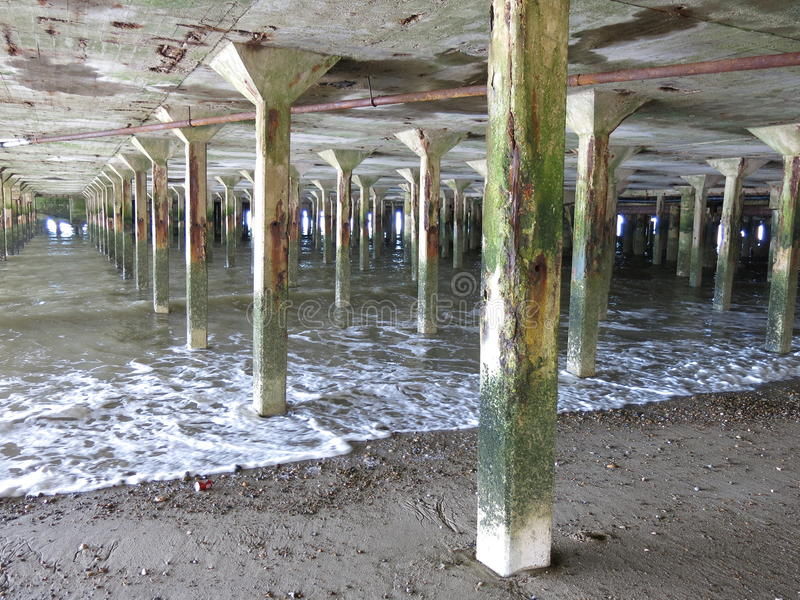 Pillars between sea and pier royalty free stock images