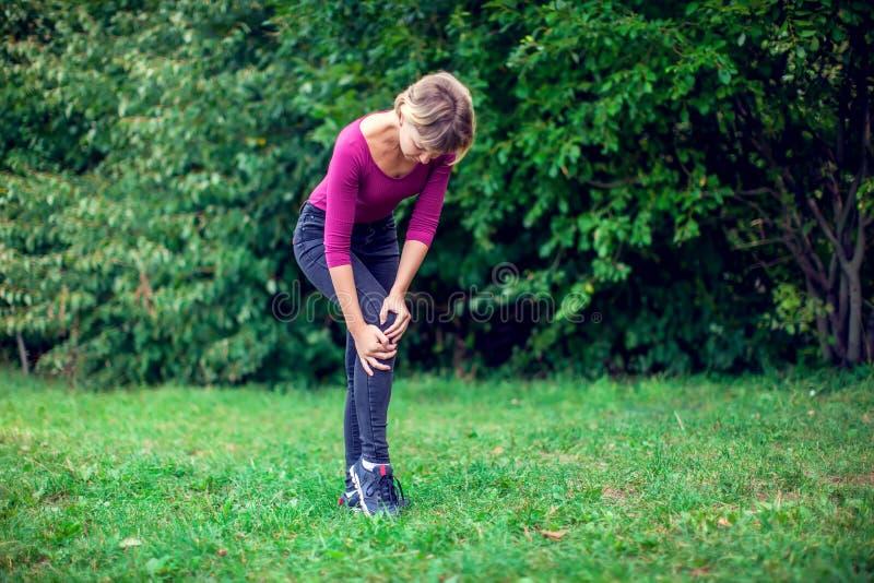 Pille im hand Frau, die unter den Schmerz im Knie im Freien leidet lizenzfreies stockfoto