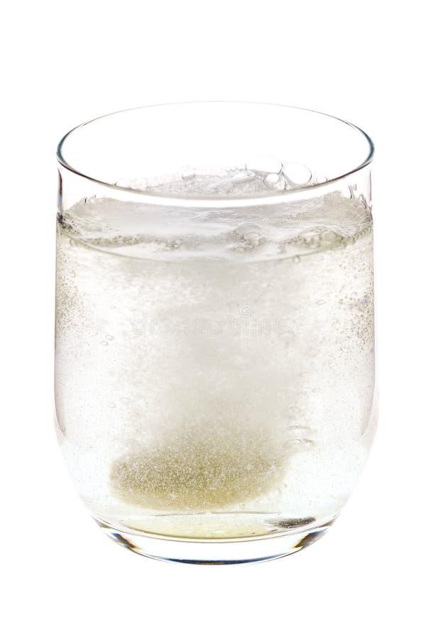 Pille sprudelnd, warf in das Glas lizenzfreie stockbilder