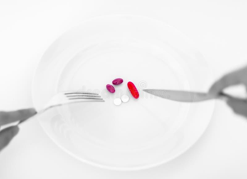 Pillen auf einer Platte mit Gabel und Messer Nähren Sie Konzept stockfotografie