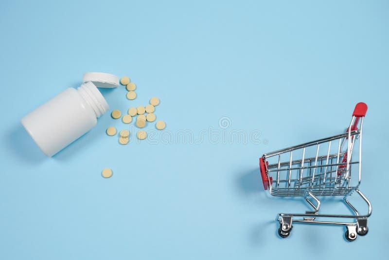 Pillen in boodschappenwagentje op blauwe achtergrond Het concept: handel binnen royalty-vrije stock fotografie