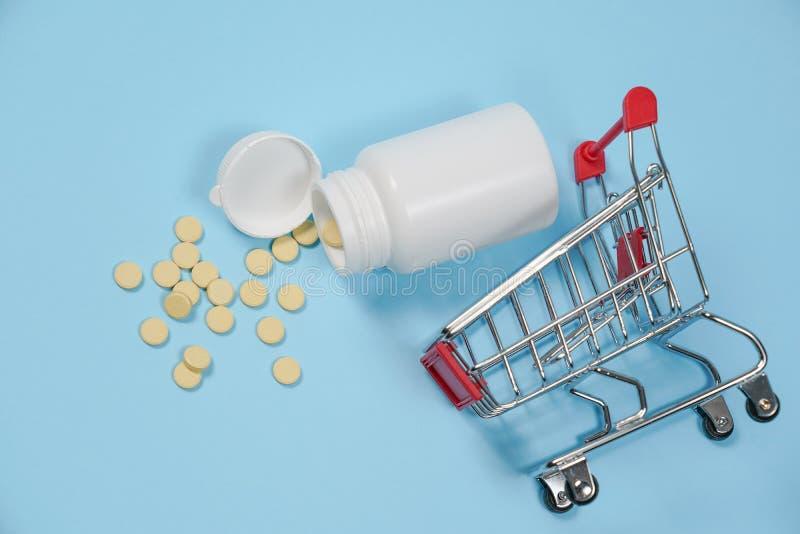 Pillen in boodschappenwagentje op blauwe achtergrond Het concept: handel in geneesmiddelen, apotheken royalty-vrije stock afbeeldingen