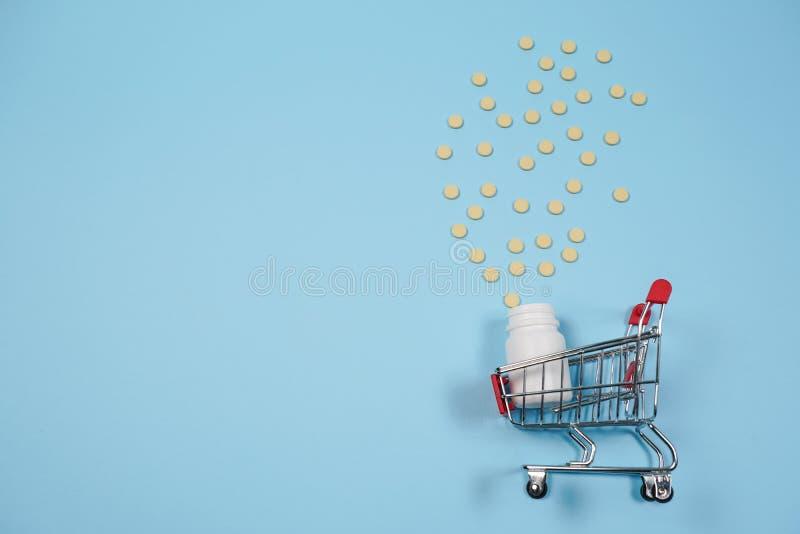 Pillen in boodschappenwagentje op blauwe achtergrond Het concept: handel in geneesmiddelen, apotheken stock foto