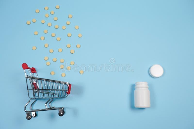 Pillen in boodschappenwagentje op blauwe achtergrond Het concept: handel in geneesmiddelen, apotheken stock afbeeldingen