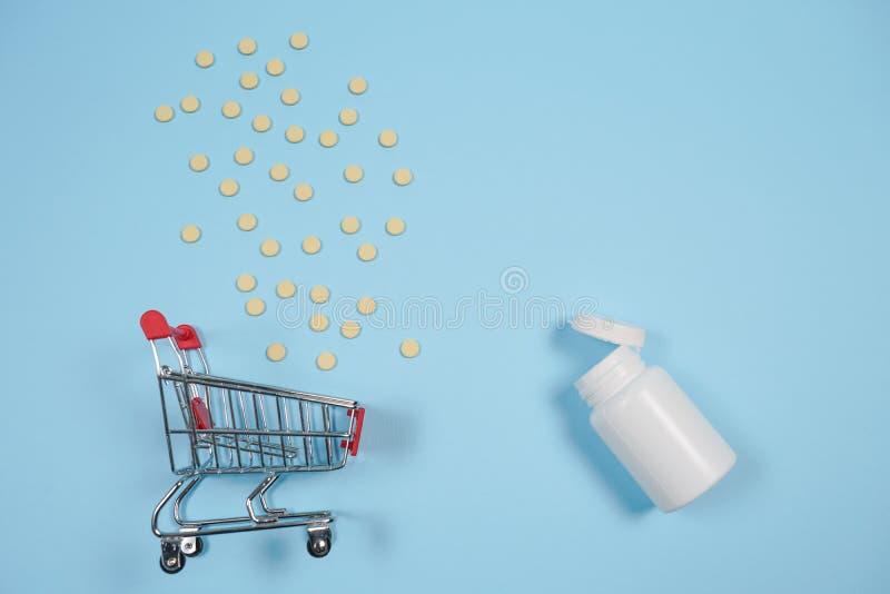 Pillen in boodschappenwagentje op blauwe achtergrond Het concept: handel in geneesmiddelen, apotheken stock afbeelding