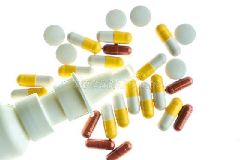 Pillen, capsules en neusnevel tegen witte terug aangestoken achtergrond royalty-vrije stock foto's