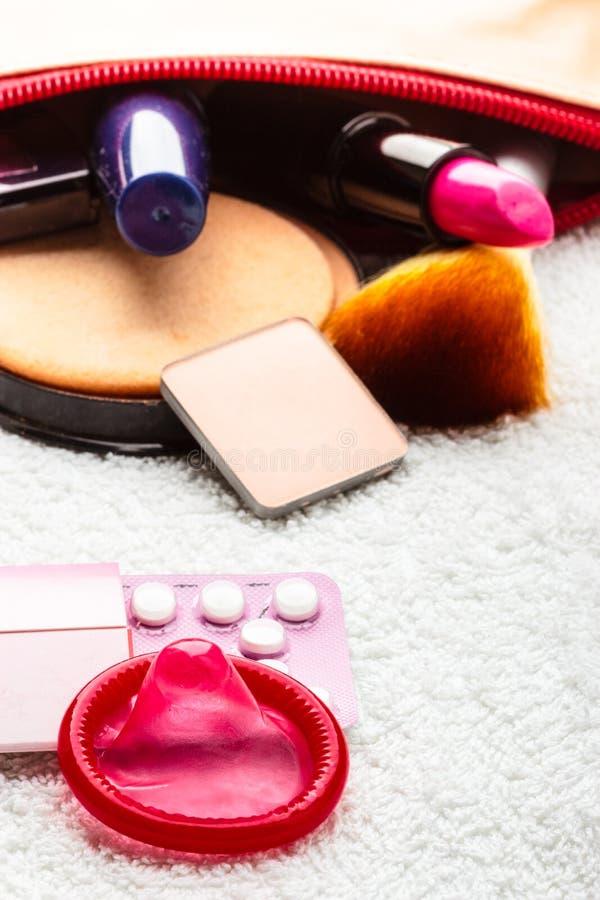 Pillen, condoom en schoonheidsmiddelen in handtas stock foto's